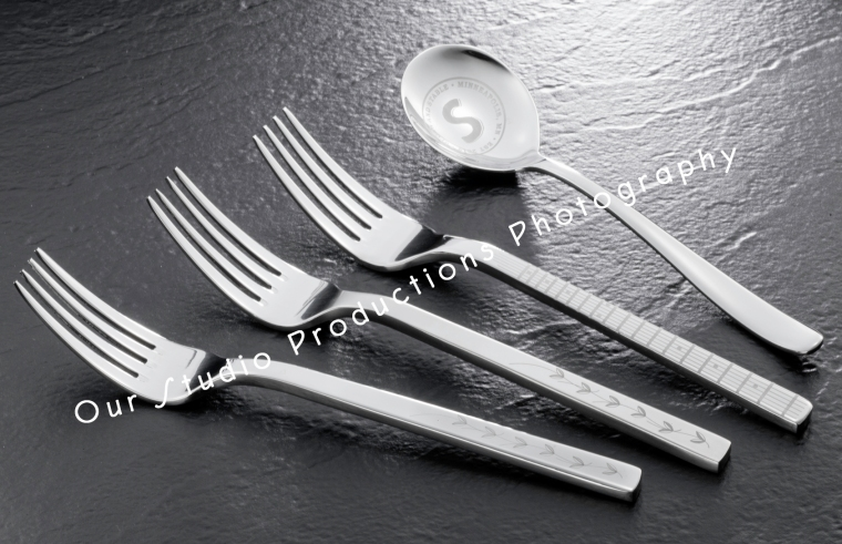 Photo of flatware on black slate.